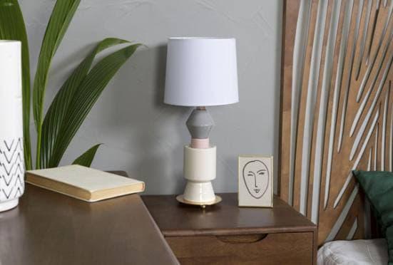 Lámpara de mesa de cerámica en color blanco, gris y rosa en dormitorio clásico de madera