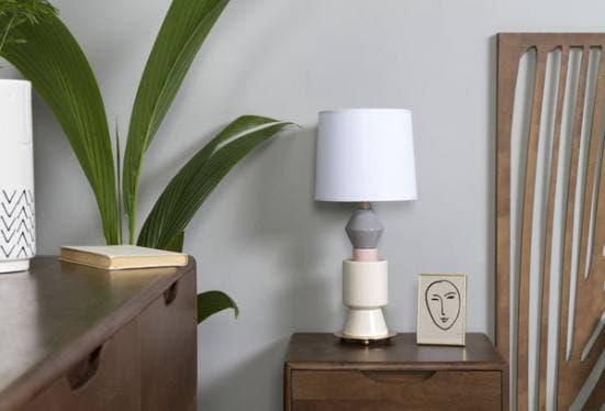 Lámpara de mesa de cerámica en color blanco, gris y rosa en dormitorio de madera